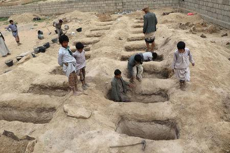 Boys inspect graves prepared for victims of Thursday's air strike in Saada province