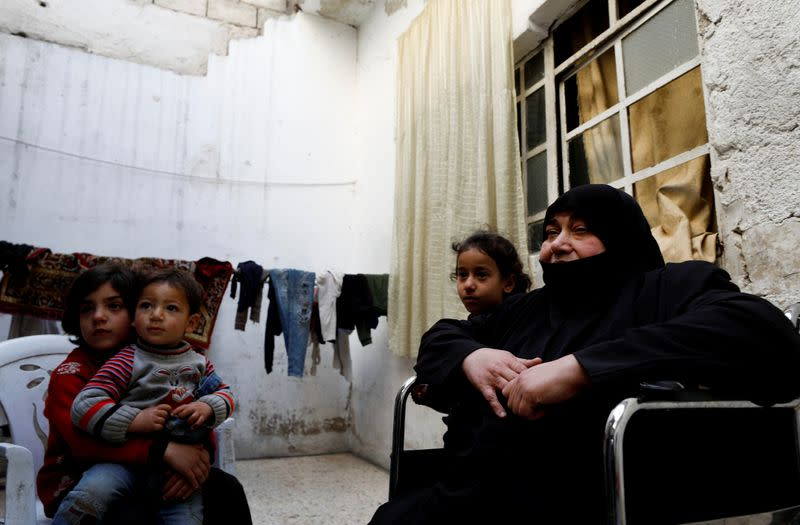 Seham Hamu, 74-year old grandmother sits on a wheelchair next to her grandchildren in Douma