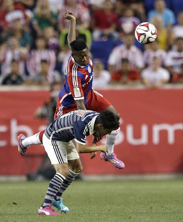 Bayern Munich's David Alaba, top, climbs over Chivas' Angel Reyna to head the ball during the first half of an international friendly soccer match at Red Bull Arena, Thursday, July 31, 2014, in Harrison, N.J. (AP Photo/Julio Cortez)