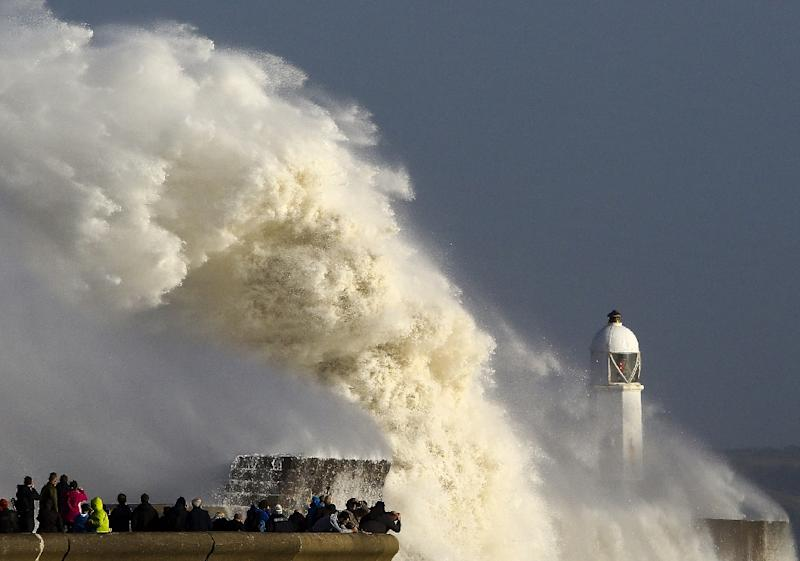 Huge waves strike the harbour wall and lighthouse at Porthcawl, south Wales, on October 16, 2017 as Storm Ophelia hits the UK and Ireland. (AFP Photo/Geoff CADDICK)