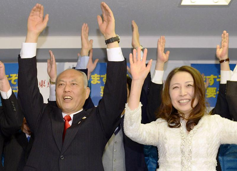 Former Health Minister Yoichi Masuzoe, left, and his wife Masami celebrate his gubernatorial election victory at his election office in Tokyo, Sunday, Feb. 9, 2014. Masuzoe, backed by Japan's ruling party, won Tokyo's gubernatorial election on Sunday, defeating two candidates who had promised to end nuclear power. (AP Photo/Kyodo News) JAPAN OUT, MANDATORY CREDIT