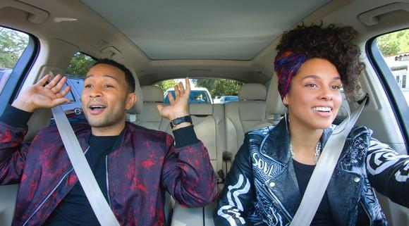 Apple series Carpool Karaoke with John Legend and Alicia Keys in the front seat of a car singing.