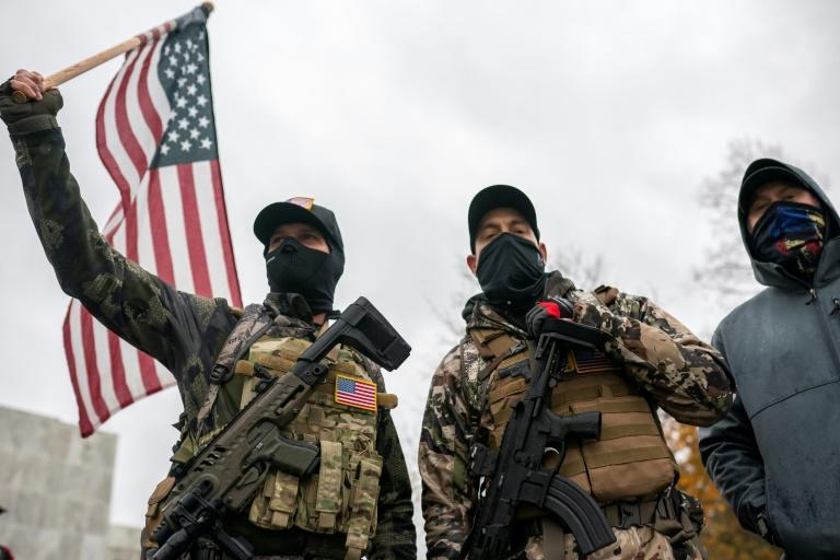 Armed protesters wave the US flag as they allege that President Donald Trump is being cheated out of an election victory in a November 14, 2020 rally in Salem, Oregon