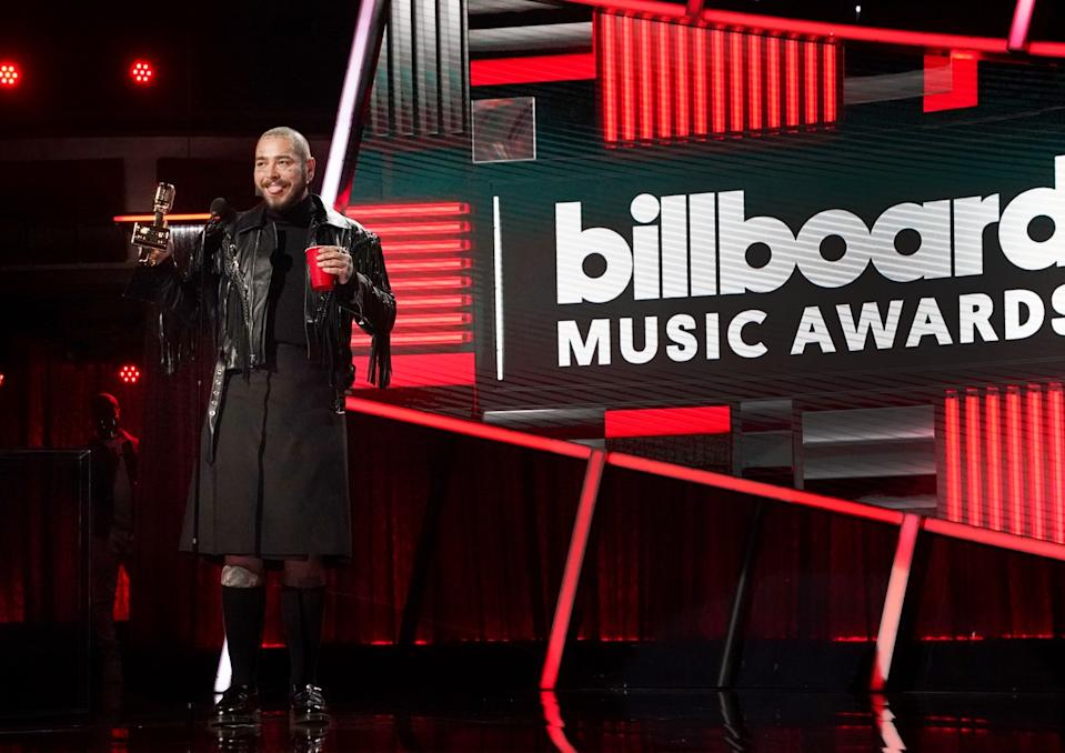 Post Malone, in fringed black leather jacket and black pleated knee-length skirt, speaks at the awards.