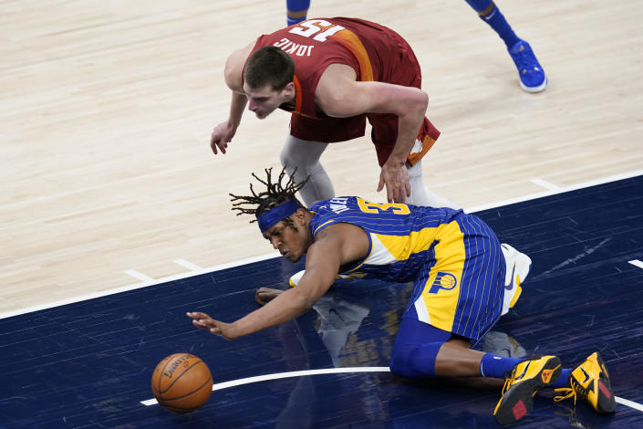 Denver Nuggets' Nikola Jokic (15) and Indiana Pacers' Myles Turner (33) battle for a loose ball during the second half of an NBA basketball game, Thursday, March 4, 2021, in Indianapolis. (AP Photo/Darron Cummings)