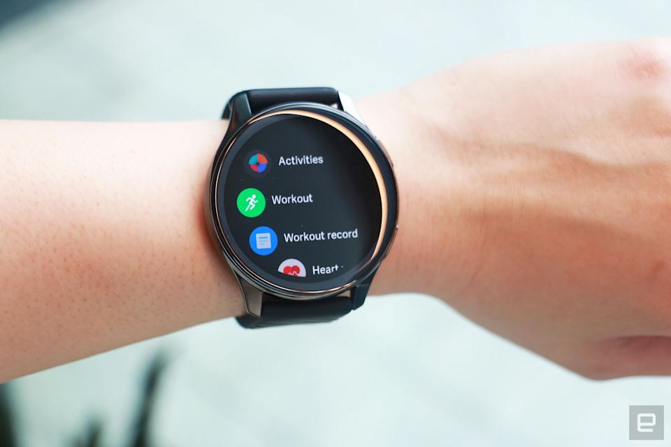 OnePlus Watch review photos. OnePlus Watch on a wrist with display showing a list of apps including Activities, Workout, Workout record and Heart...