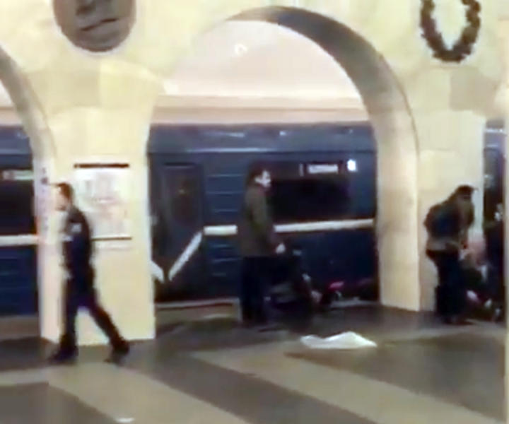 In this grab taken from AP video, Russian police officer, left, and people walk past the damaged train at the Tekhnologichesky Institut subway station in St.Petersburg, Russia, Monday, April 3, 2017. The subway in the Russian city of St. Petersburg is reporting that several people have been injured in an explosion on a subway train. (AP video via AP)