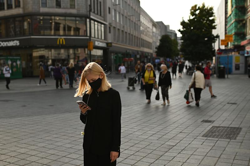 People walk through Liverpool city centre as new local restrictions are confirmed (AFP via Getty Images)
