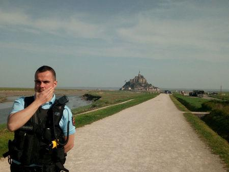 French gendarme is seen near Mont Saint-Michel as it was closed and evacuated after a man threatened he installed a bomb on the island, in Mont-Saint-Michel, France, in this image obtained from social media, April 22, 2018. Courtesy of INSTAGRAM/ @ROMANKAGILLETTE/via REUTERS