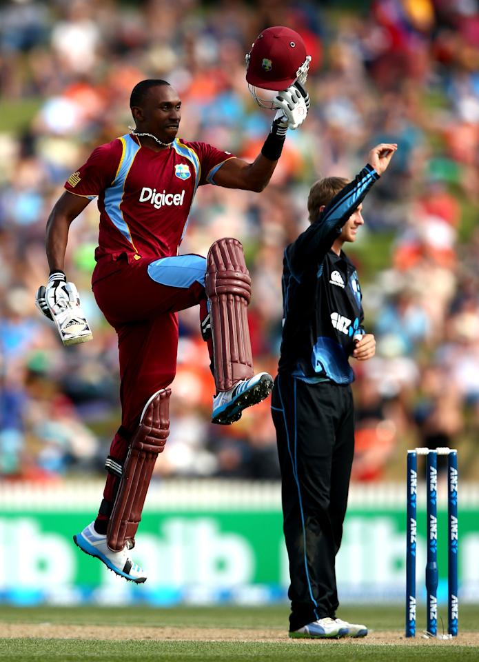 HAMILTON, NEW ZEALAND - JANUARY 08:  Dwayne Bravo of the West Indies celebrates his century as Kane Williamson of New Zealand looks on during game five of the One Day International Series between New Zealand and the West Indies at Seddon Park on January 8, 2014 in Hamilton, New Zealand.  (Photo by Phil Walter/Getty Images)