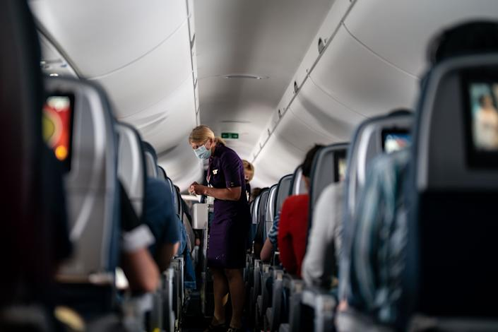 Flight attendants hand out refreshments to a packed Delta Airlines flight on Friday, May 21, 2021. (Kent Nishimura / Los Angeles Times via Getty Images)