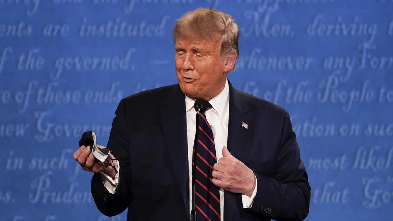 President Donald Trump holds out his face mask during the first presidential debate Tuesday, Sept. 29, 2020, at Case Western University and Cleveland Clinic, in Cleveland, Ohio. (Julio Cortez/AP)