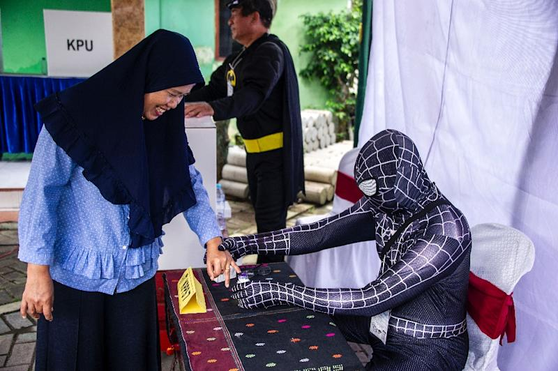 Election officials dressed as cartoon superheroes in Surabaya to encourage voters to come to the polling station (AFP Photo/Juni Kriswanto)