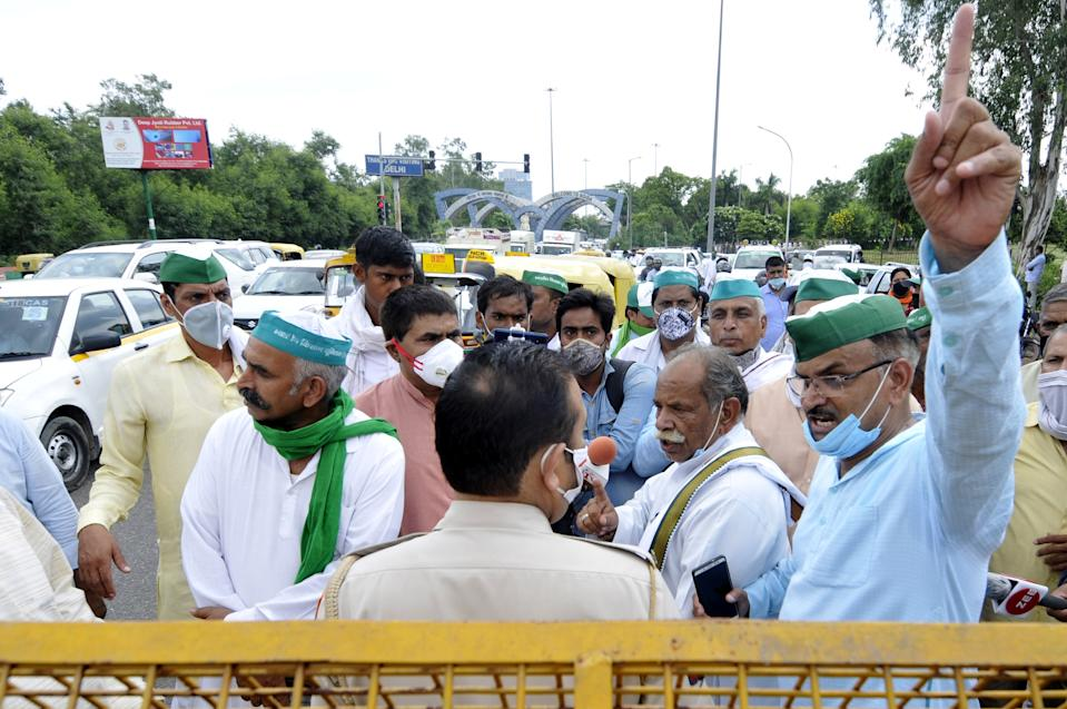 Members of the Bharatiya Kisan Union (BKU) Bhanu speak with police personnel at Sector 14A Noida Delhi border where the police placed barricades to stop them from proceeding towards Azadpur Mandi on September 23, 2020 in Noida, India. (Photo by Sunil Ghosh/Hindustan Times via Getty Images)