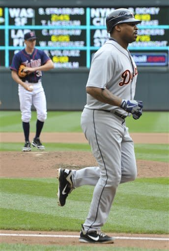 Detroit Tigers' Delmon Young heads home after hitting a two-run home run off Minnesota Twins pitcher Cole DeVries, left, in the fourth inning of a baseball game, Wednesday, Aug. 15, 2012, in Minneapolis. (AP Photo/Jim Mone)