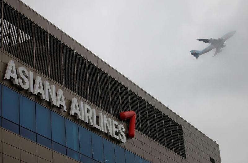 FILE PHOTO: Aircraft flies over the head office of Asiana Airlines in Seoul