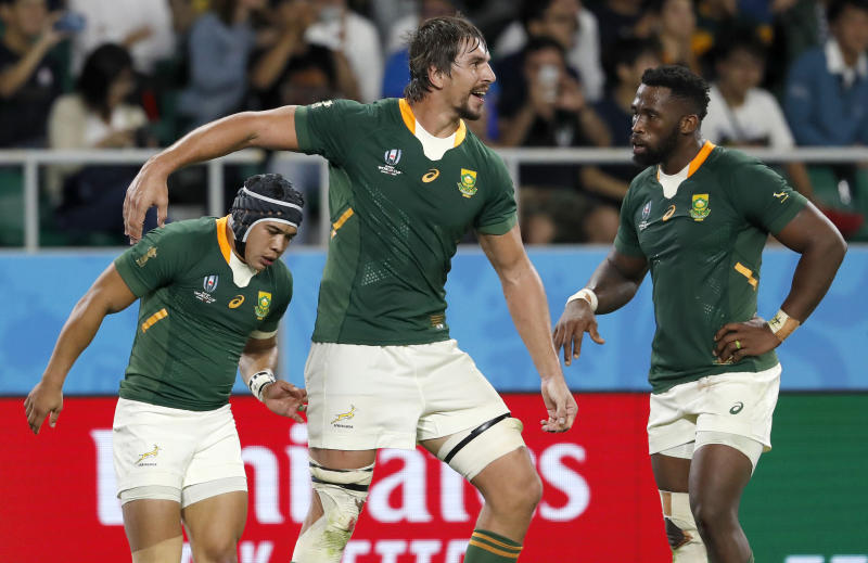 South Africa's Cheslin Kolbe, left, is congratulated by teammates Eben Etzebeth and Siya Kolisi, right, after scoring a try during the Rugby World Cup Pool B game at Shizuoka Stadium Ecopa between South Africa and Italy, in Shizuoka, Japan, Friday, Oct. 4, 2019. (AP Photo/Shuji Kajiyama)