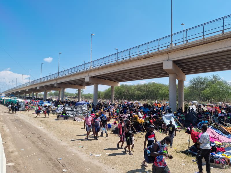 Migrants shelter under the Del Rio International Bridge which connects with Mexico