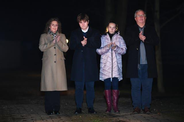 Captain Sir Tom Moore's daughter Hannah Ingram-Moore, grandson Benji, granddaughter Georgia and son-in-law Colin Ingram outside his home in Marston Moretaine, Bedfordshire, joining in with a nationwide clap in honour of the 100-year-old charity fundraiser who died on Tuesday after testing positive for Covid-19
