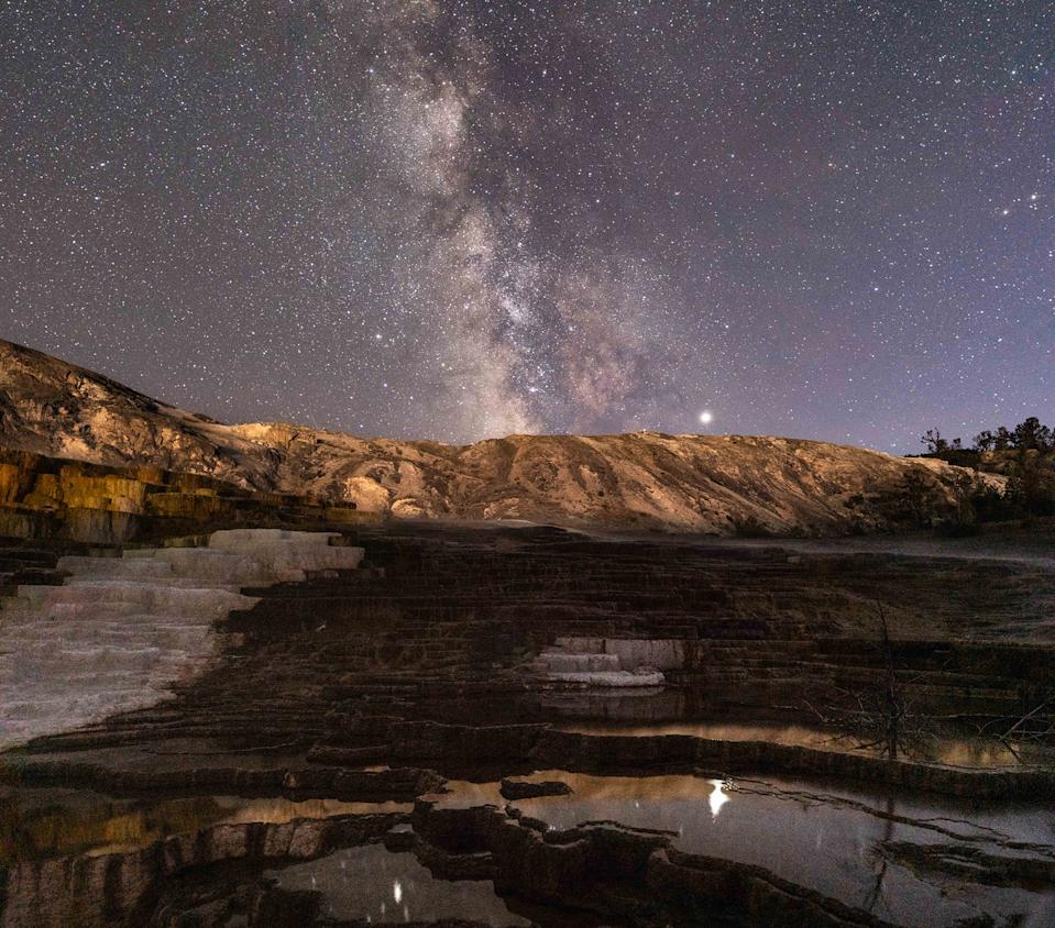 "The Milky Way shimmers over Yellowstone National Park in this starry night-sky photo by Chirag Upreti. This panorama combines 10 frames captured from the ""Mound and Jupiter Terrace"" at Mammoth Hot Springs, and it features an excellent view of the planet Jupiter, shining brightly to the right of the Milky Way while reflecting off the surface of the water below. Saturn is also visible in the photo, shining to the left of the Milky Way, directly above the asterism known as the Teapot."