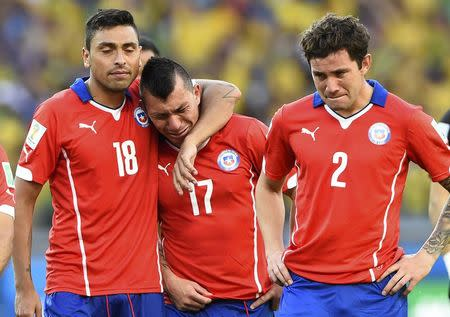 Chile's Gonzalo Jara, Gary Medel and Eugenio Mena (L-R) react after losing their 2014 World Cup round of 16 game against Brazil at the Mineirao stadium in Belo Horizonte June 28, 2014. REUTERS/Dylan Martinez