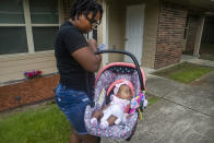 Tyesha Young, who lost her hospital job during the pandemic, arrives home with her baby Jalayah Johnson in Waggaman, La., Friday, July 2, 2021. More than $7,000 behind on rent, Young had hoped a program in Louisiana would bail her out and allow her family to avert eviction in the coming weeks. But the 29-year-old mother of two from Jefferson Parish is still waiting to hear whether any of the $308 million available from the state for rental assistance and utility payments will give her a lifeline. She applied for money last year but never heard anything. (AP Photo/Sophia Germer)