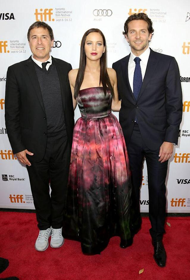 """<p>Lawrence followed up her <i>Hunger Games </i>success with a starring role in romantic comedy-drama <i>Silver Linings Playbook</i> alongside <a href=""""https://www.yahoo.com/entertainment/tagged/bradley-cooper"""" data-ylk=""""slk:Bradley Cooper"""" class=""""link rapid-noclick-resp"""">Bradley Cooper</a> (right), directed by David O. Russell (left). The film premiered at the Toronto Film Festival on Sept. 8, 2012. (Photo: Getty Images) </p>"""