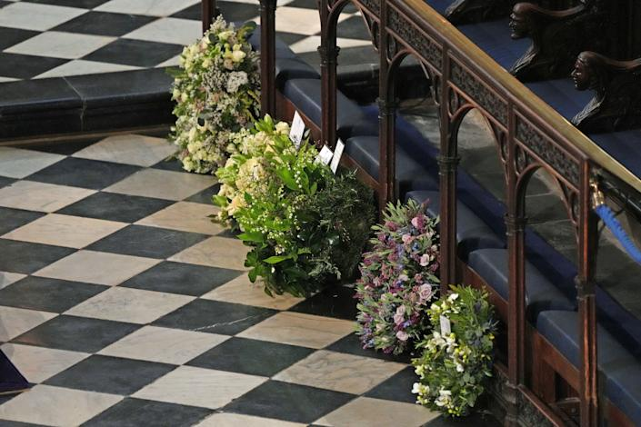 Wreaths from members of the royal family lie against the pews during the funeral.