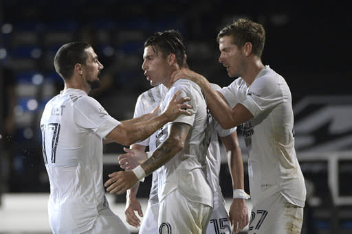 LA Galaxy forward Cristian Pavon, center, is congratulated by midfielders Sebastian Lletget (17) and Emil Cuello (27) after scoring on a penalty kick during the first half of an MLS soccer match against Los Angeles FC, Saturday, July 18, 2020, in Kissimmee, Fla. (AP Photo/Phelan M. Ebenhack)