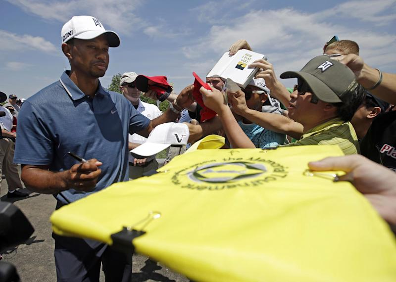 Tiger Woods signs autographs for fans after playing in the pro-am of the Memorial golf tournament Wednesday, May 29, 2013, in Dublin, Ohio. (AP Photo/Darron Cummings)