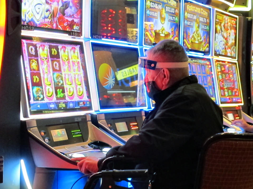A man wears a face shield while playing a slot machine at the Golden Nugget casino in Atlantic City, N.J. on July 2, 2020. A report released Nov. 16, 2020 by the national trade association for the U.S. casino industry found that America's casinos won 81% of the amount of money during the third quarter of this year that they did in the third quarter of 2019, when there was no virus pandemic. (AP Photo/Wayne Parry)
