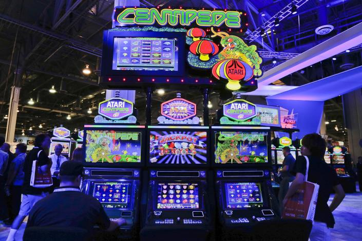 Gaming industry representatives sit to play the Centipede video game slot machine at the Global Gaming Expo, Wednesday, Sept. 25, 2013, in Las Vegas. The first generation of joystick-controlled, penny arcade-themed gambling machines broadcasts the gambler's performance on an overhead screen, and pays out points in cash. (AP Photo/Julie Jacobson)