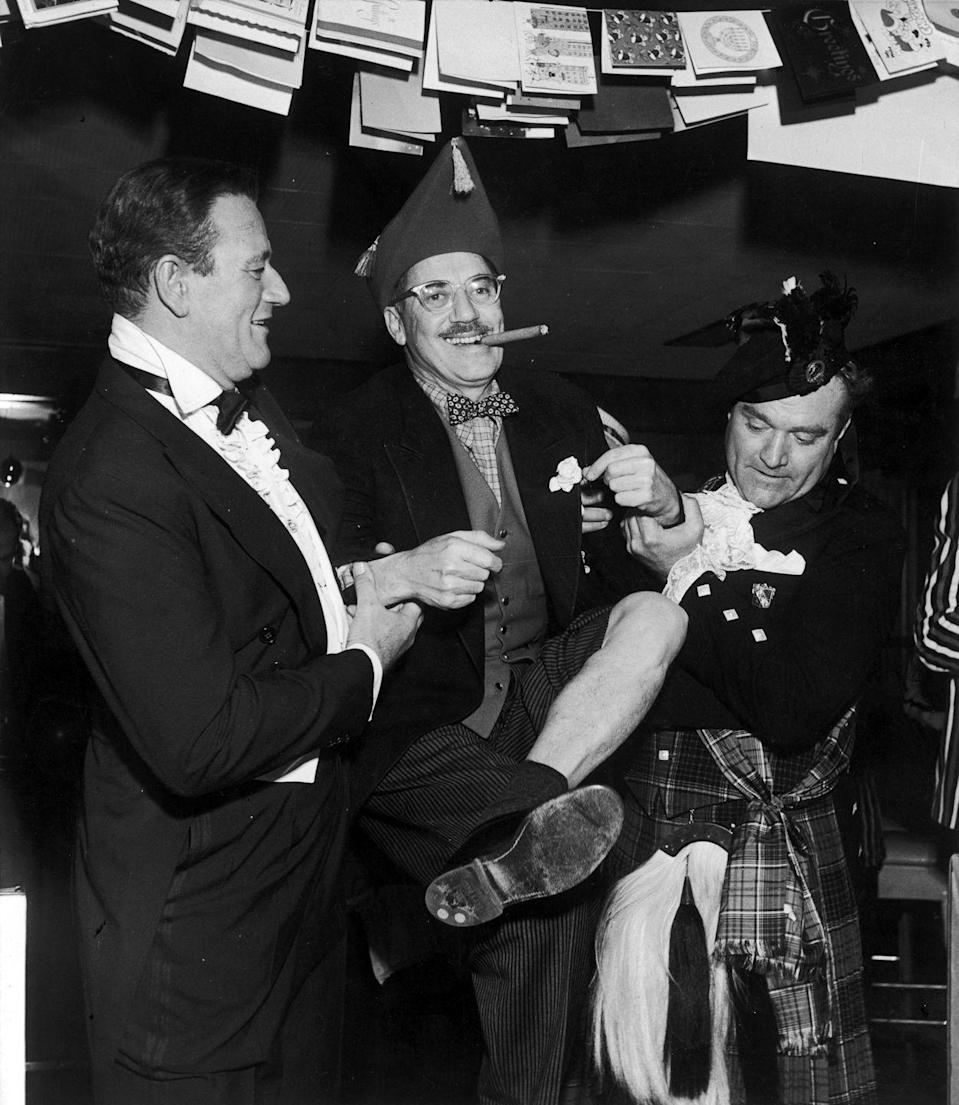 <p>Western star, John Wayne, has a rowdy good time with comedians Groucho Marx and Red Skelton underneath a string of holiday cards at a party in 1955.</p>