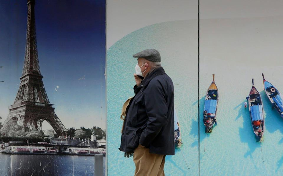 A man wearing a face mask walks by a closed travel agency in Lisbon - Armando Franca/AP
