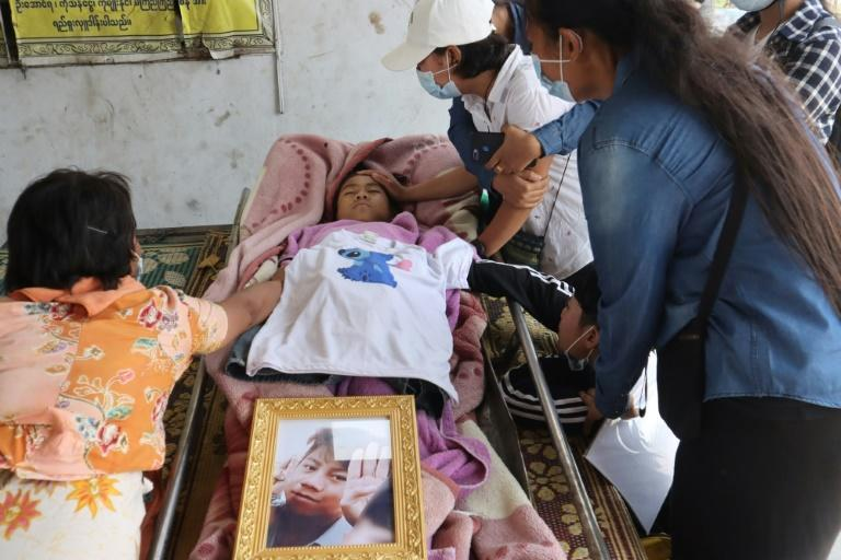Family members grieve over the body of teenage bystander Tun Tun Aung at a cemetery in Mandalay on Tuesday, a day after he was shot dead in front of his home by security forces during a crackdown on demonstrations against the military coup