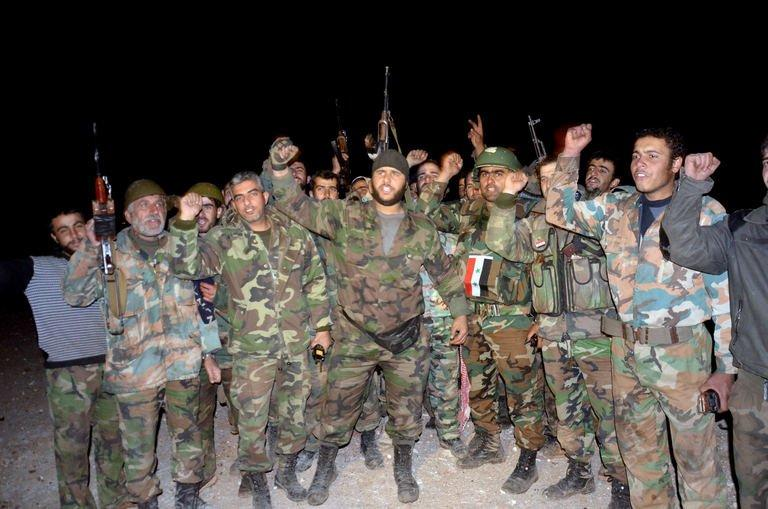 Pro-government forces celebrate their alleged victory in a battle against rebels at the Air Defence Base in Tal Hassil, 15 kms from Aleppo Airport, on December 30, 2012. Violence ravaged Syria into 2013 with the gruesome discovery of dozens of tortured, headless corpses in a Damascus district, clouding end-of-year efforts by peace envoy Lakhdar Brahimi to end 21 months of bloodshed