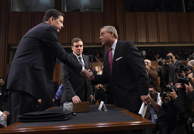 <p>Former FBI Director James Comey is welcomed by Committee Chairman Senator Richard Burr (R) and Vice Chairman Senator Mark Warner (C) to a US Senate Select Committee on Intelligence hearing on Capitol Hill in Washington, D.C., June 8, 2017. (Photo: Saul Loeb/AFP/Getty Images) </p>