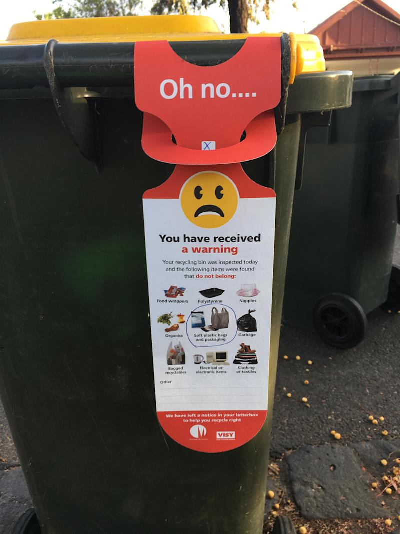 recycling bin warning with frowning face attached to bin in Moreland, Melbourne