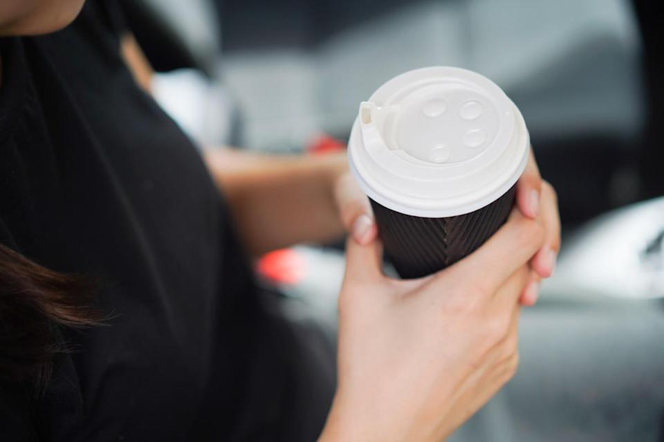 Young woman holding take out coffee cup in car