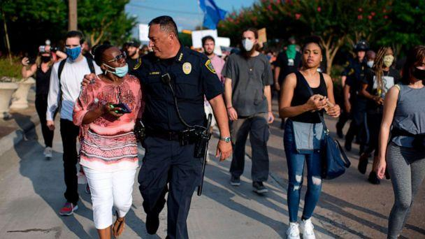 PHOTO: Houston Police Chief Art Acevedo walks arm-in-arm with a woman during a 'Justice for George Floyd' event in Houston, Texas, May 30, 2020, after George Floyd died while being arrested and pinned to the ground by a Minneapolis police officer. (Mark Felix/AFP via Getty Images)