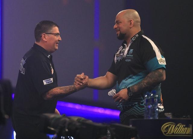 Gary Anderson, left, defeated Devon Petersen to reach the quarter-finals of the PDC World Darts Championship (Adam Davy/PA)