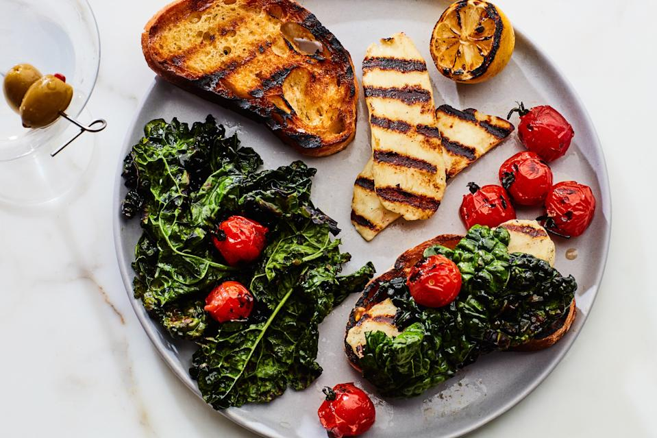 """Pile charred Halloumi cheese, kale, and cherry tomatoes onto grilled bread rubbed with garlic for an <a href=""""https://www.epicurious.com/expert-advice/grilled-greens-for-dinner-article?mbid=synd_yahoo_rss"""" rel=""""nofollow noopener"""" target=""""_blank"""" data-ylk=""""slk:almost-instant meal"""" class=""""link rapid-noclick-resp"""">almost-instant meal</a> in the backyard. <a href=""""https://www.epicurious.com/recipes/food/views/grilled-greens-and-cheese-on-toast?mbid=synd_yahoo_rss"""" rel=""""nofollow noopener"""" target=""""_blank"""" data-ylk=""""slk:See recipe."""" class=""""link rapid-noclick-resp"""">See recipe.</a>"""