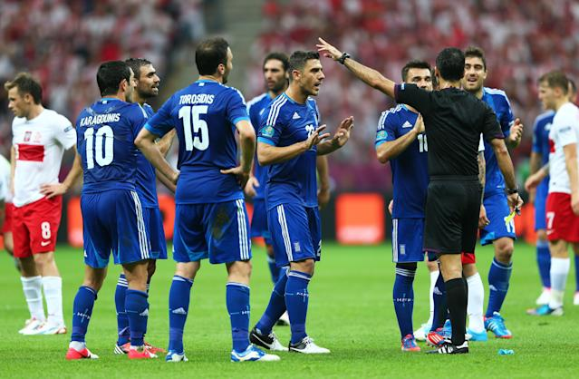 WARSAW, POLAND - JUNE 08: The Greek players appeal to the Referee Carlos Velasco Carballo as Sokratis Papastathopoulos of Greece (R) is shown a second yellow card and sent off during the UEFA EURO 2012 group A match between Poland and Greece at The National Stadium on June 8, 2012 in Warsaw, Poland. (Photo by Michael Steele/Getty Images)