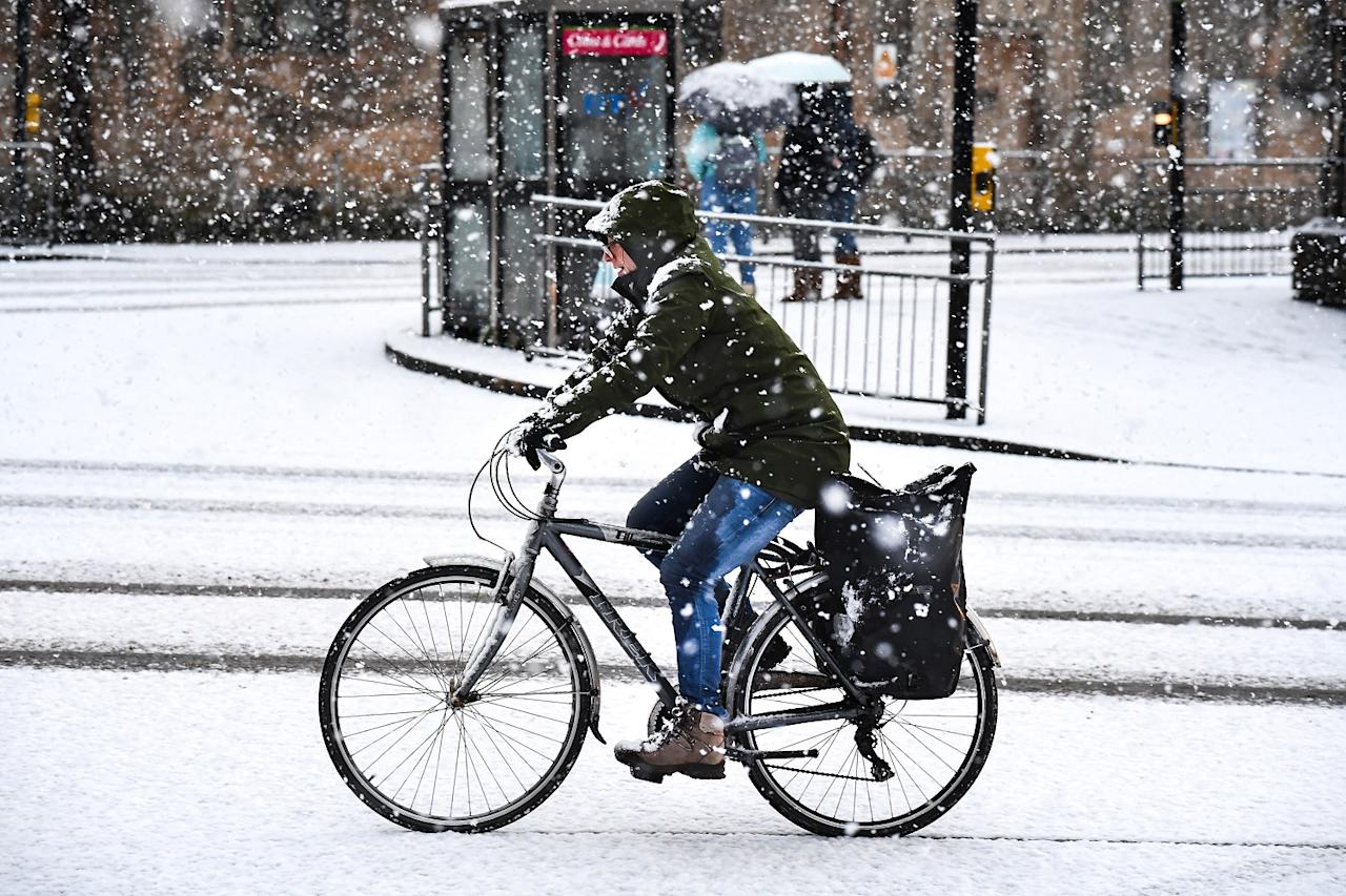 <p>A man rides his bike through a snow covered street. (Getty) </p>