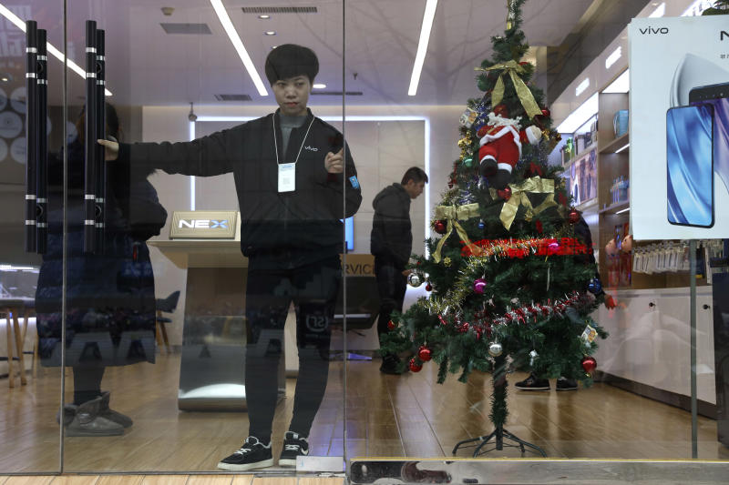In this Saturday, Dec. 22, 2018, photo, a sales person waits for customers near a Christmas tree decoration in Zhangjiakou in northern China's Hebei province. At least four Chinese cities and one county have ordered restrictions on Christmas celebrations this year. Churches in another city have been warned to keep minors away from Christmas, and at least ten schools nationwide have curtailed Christmas on campus, The Associated Press has found. (AP Photo/Ng Han Guan)