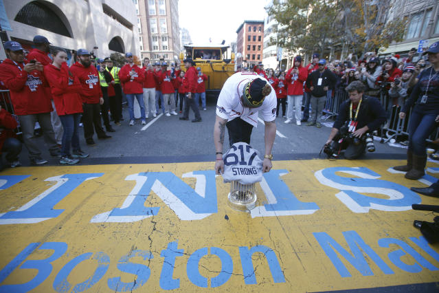 Boston Red Sox's Jonny Gomes places the 2013 World Series trophy and a Red Sox baseball jersey at the Boston Marathon Finish Line. (AP Photo/Elise Amendola)