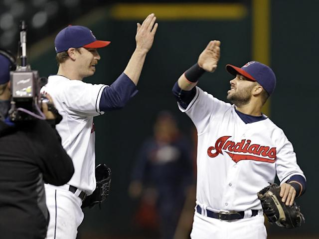 Cleveland Indians first baseman Nick Swisher, right, celebrates with relief pitcher John Axford after a 5-3 win over the Kansas City Royals in a baseball game on Wednesday, April 23, 2014, in Cleveland. (AP Photo/Mark Duncan)