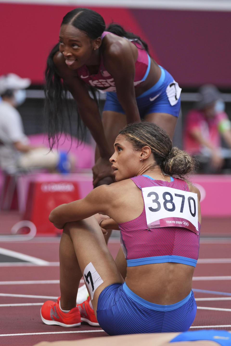 Sydney McLaughlin, bottom, of the United States, and teammate Dalilah Muhammad look at the scoreboard after the final of the women's 400-meter hurdles at the 2020 Summer Olympics, Wednesday, Aug. 4, 2021, in Tokyo. (AP Photo/Matthias Schrader)