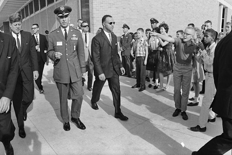 """FILE - In this Nov. 21, 1963 file photo, President John F. Kennedy walks past young bystanders during his visit to San Antonio. """"Our goal must be an educational system in the spirit of the declaration of independence - a system in which all are created equal,"""" Kennedy said in a graduation speech at San Diego State College on June 11, 1963. """"A system in which every child, whether born a banker's son in a Long Island mansion, or a Negro sharecropper's son in an Alabama cotton field, has every opportunity for an education that his abilities and character deserve."""" (AP Photo/Houston Chronicle)"""
