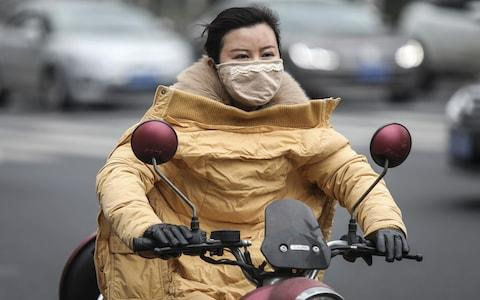 A woman wears a mask while riding an electric bicycle  - Credit: Getty